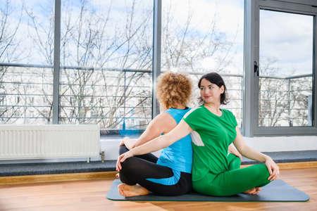 Two sportive women hug in light gym