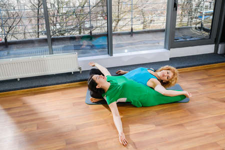 Two women make yoga stretching together indoors