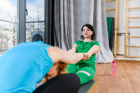Two female sportive friends stretch each other
