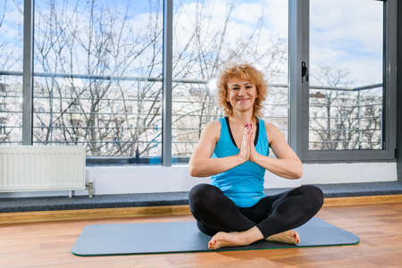 Curly smiling fit woman exercise yoga indoors