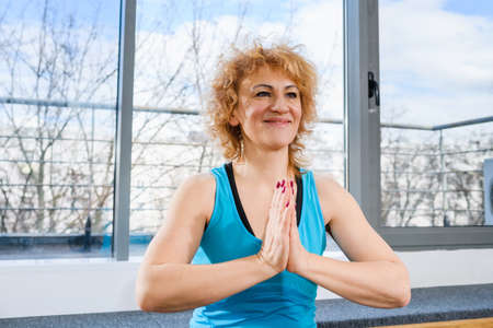 Middle age blonde woman sit in lotus yoga pose with hands in namaste gesture on sport mat at light fitness studio