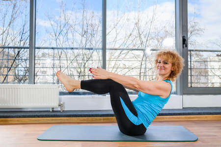 Middle age fit woman exerise yoga stretching