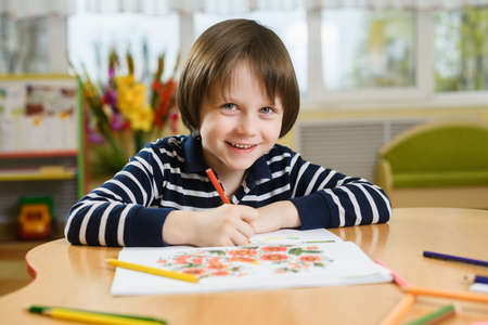 Smiling preschool boy draws in his notebook. The boy sits at the table and holds a pencil in his hand.