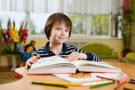 A preschool boy is reading a huge book. The book lies on the table among the pencils. The boy looks into the camera and smiles. 스톡 콘텐츠