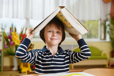 A preschool boy raised a huge book above his head and looked into the camera with a smile.