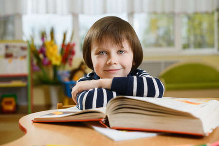 Preschool boy leaning his elbows on large book and smiles looking forward. 스톡 콘텐츠