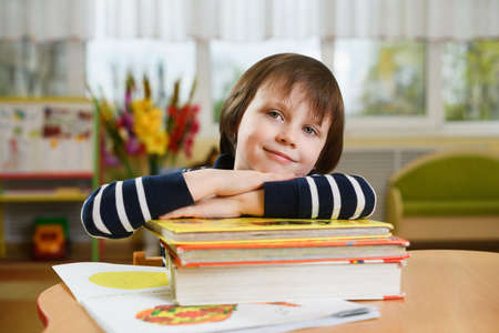 Preschool boy leaning his elbows on stack of school books.