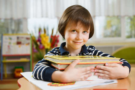 Preschool boy hugging stack of books and smiling looking forward