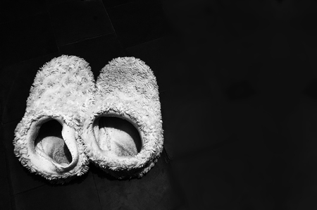 White slippers on a black background. Creative concept.