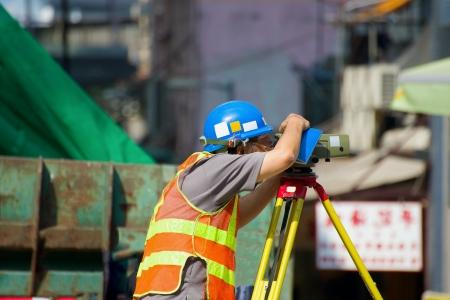 teodolito: Trabajador con la medición del teodolito en la construcción de Hong Kong Foto de archivo