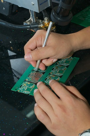 hands of the Chinese worker engraves plate for microchips in the factory. photo