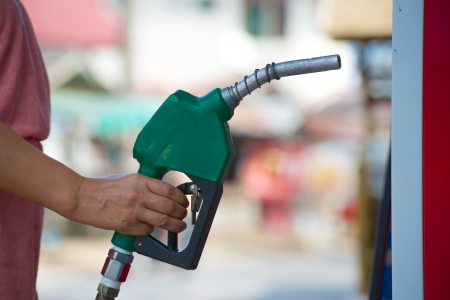 petrol station: green fuel pipe in hand