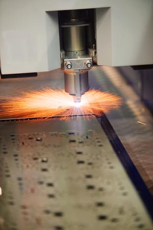 corte laser: Corte por l�ser industrial de chapa de acero con chispas, foto real