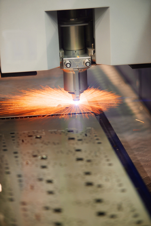Industrial Laser cutting of steel metal sheet with sparks, real photo photo