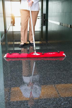 クリーナーの労働者は事務所ビル床をクリーニングします。