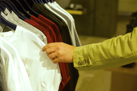 Buyer chooses shirt in trendy modern boutique