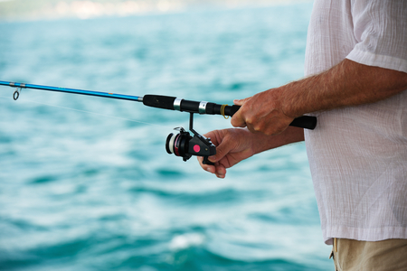 hand line fishing: Fishing on the sea: rod in fisherman hands