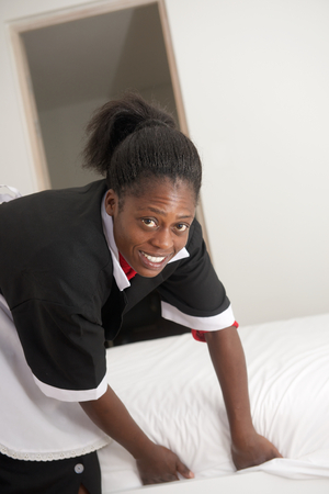 housemaid: Happy housemaid change bed sheets in room