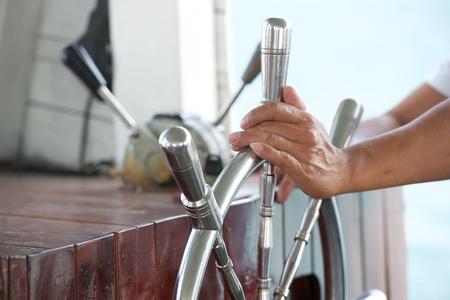 timon de barco: Las manos sostienen volante del barco en el mar tropical