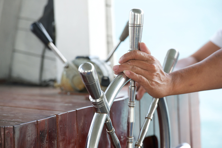 Les mains tiennent le volant du bateau en mer tropique Banque d'images