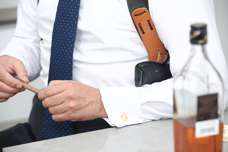 A guard with a cigar in his hand and a gun in shoulder holster