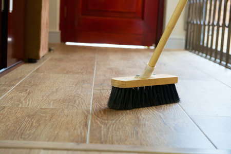 Cleaning broom on wooden floor in house