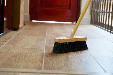 brooming: Cleaning broom on wooden floor in house
