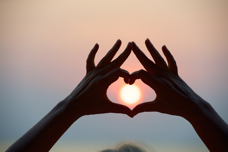 Heart symbol by hands on sea sunset. Love symbol