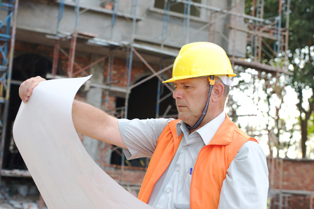 Builder in helmet with a drawing plan photo photo