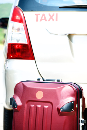 Red traveler suitcase and white taxi