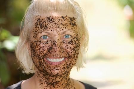 cremas faciales: Retrato de mujer con una máscara pilling café aplica en la cara para cuidado de la piel y masaje Foto de archivo