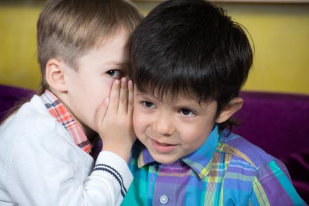 Boy is telling a secret to a friend Banco de Imagens