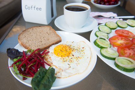 breakfast eggs: Coffee cup, scrambled eggs and salad breakfast on table