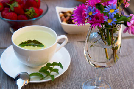 breakfast cup: Cup of green tea with lemon on table with bunch of flowers