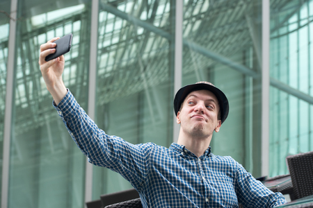 makes: Very funny hipster fellow makes selfie by mobile phone