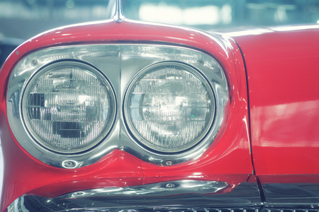 Headlamps of fashionable red retro car close-up photo