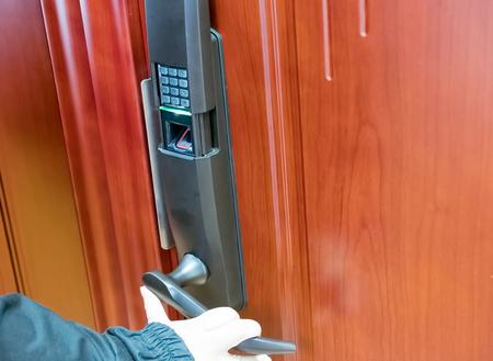 The hand opens the door with a fingerprint lock Standard-Bild - 91780111