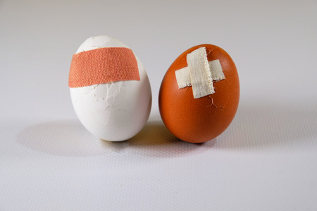 Two different color eggs with problems, injuries pasted with medical plaster Standard-Bild - 94718448