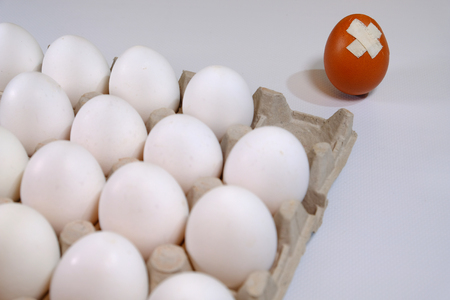 A cardboard box of white eggs and one egg of dark color is not in the box it is damaged and has problems