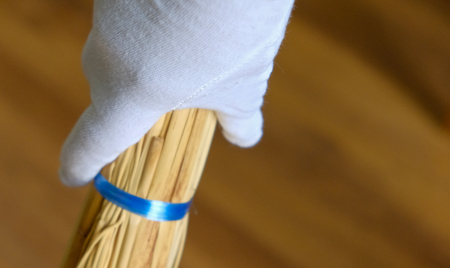 A hand in a white glove holds a broom for Cleaning and sweeping room Standard-Bild - 93464507