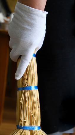 Eine Hand in einem weißen Handschuh hält einen Besen für Reinigung und Feuerzeug . Vertikales Foto Standard-Bild - 93410299
