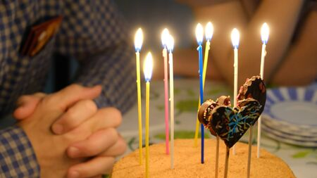 Celebrating the birthday of one of the family members, a cake with candles on the table Standard-Bild - 94065024
