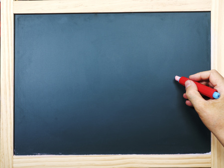 Hand with chalk at the empty blackboard