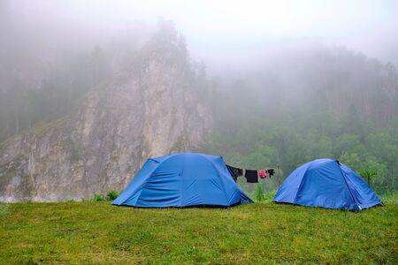 Tents stand in the mountains, morning mist