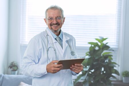 Cheerful mature doctor with a tablet in hands