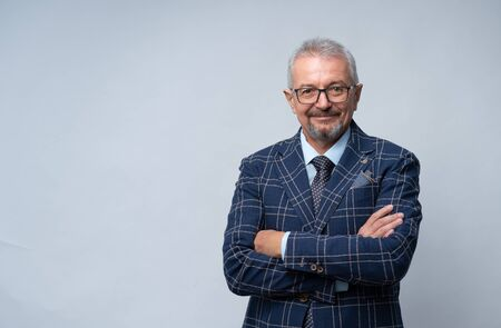 Mature man in glasses and a suit with crossed arms Banco de Imagens