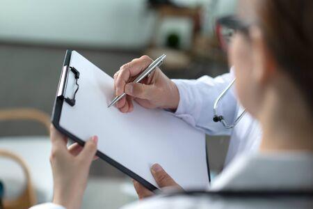 Doctor write on paper closeup photo Imagens