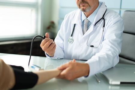 A doctor measures the blood pressure of a patient closeup photo Imagens