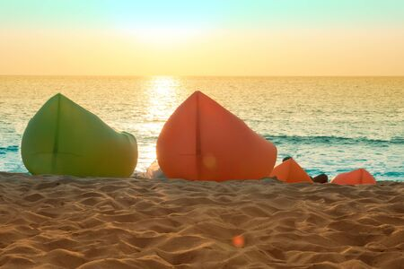 Inflatable chairs on the beach, sea, sand and evening sunset