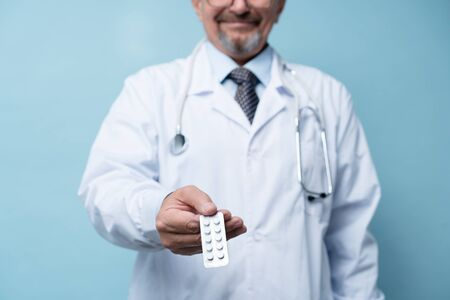 Portrait of a mature doctor standing in a hospital and holding medicine in hand - Stock Photo Banco de Imagens